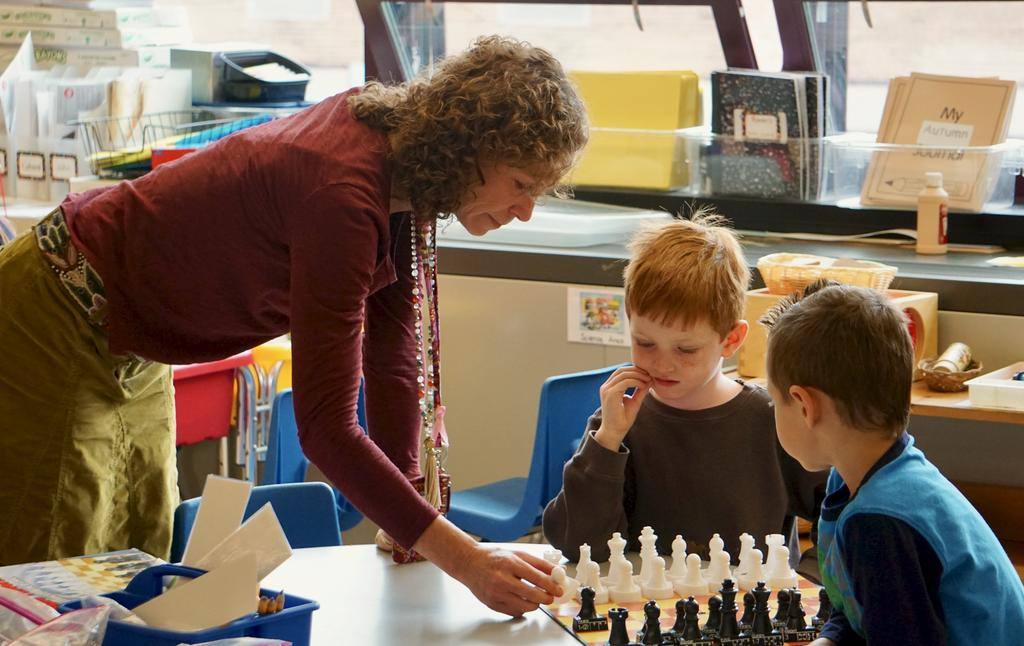 Teacher playing chess with two small boys