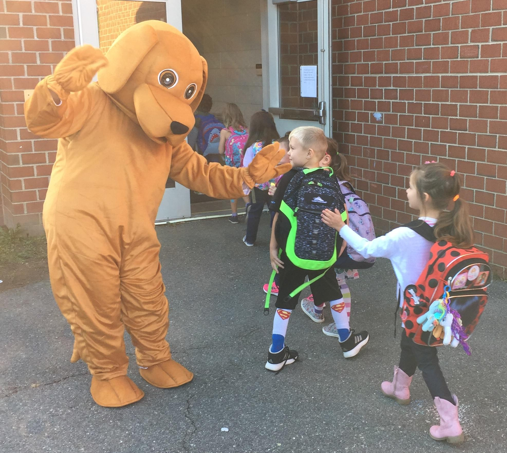 Goldie, our school mascot, greeting students with a high five as they enter the school building.