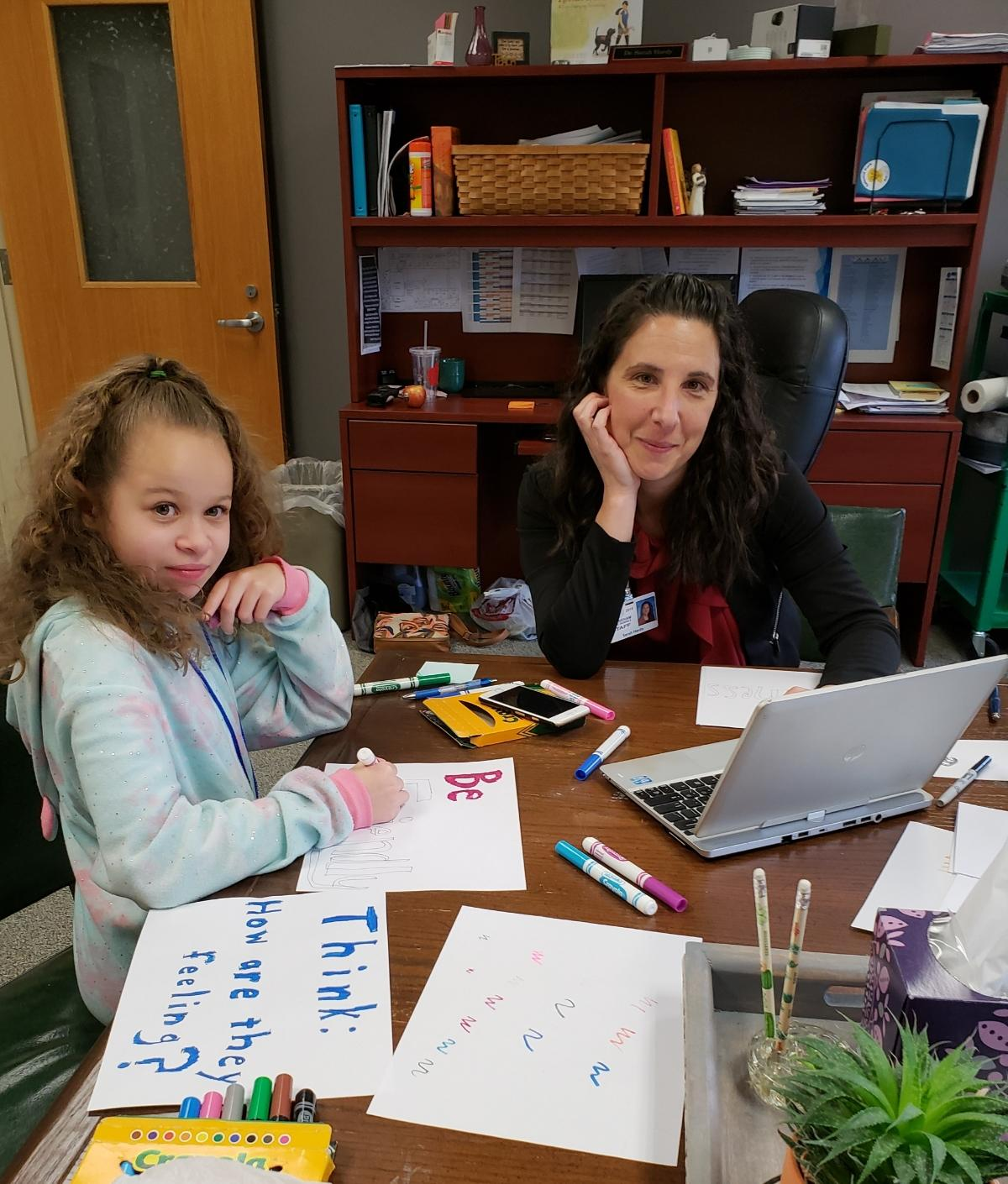 Dr. Sarah Hardy working at a table in her office with a fourth grade student (female).