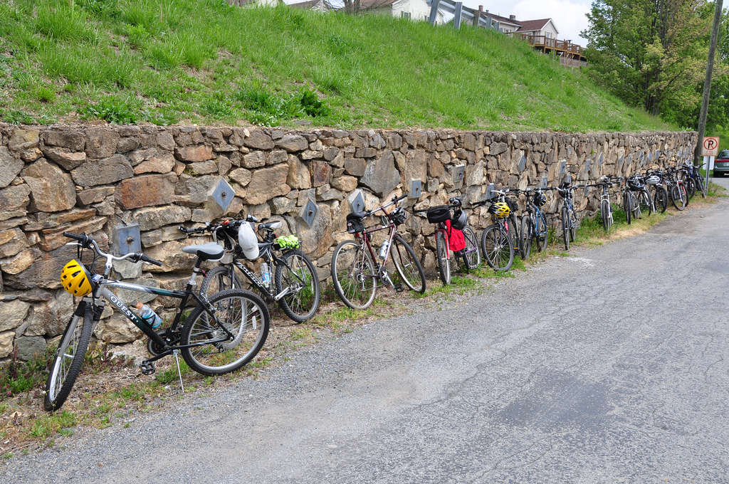 Row of bikes leaning against a stone wall.