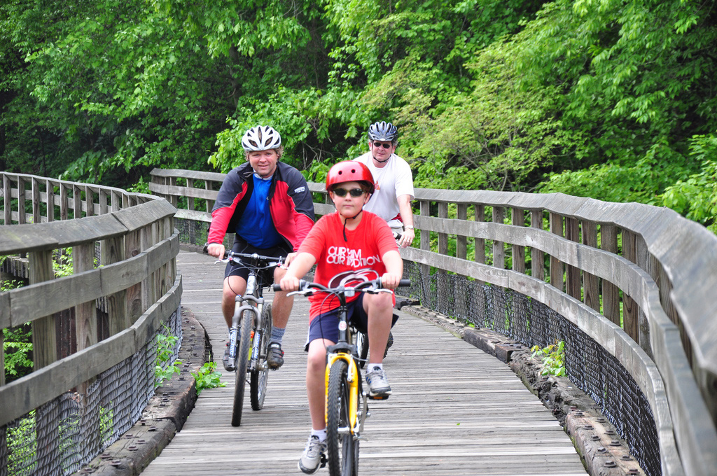 Two adults and one child riding bikes over a wooden trail bridge.