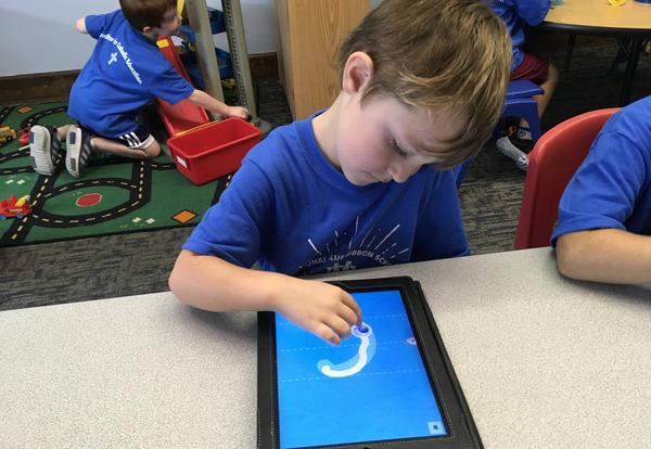 Student tracing letters on a tablet