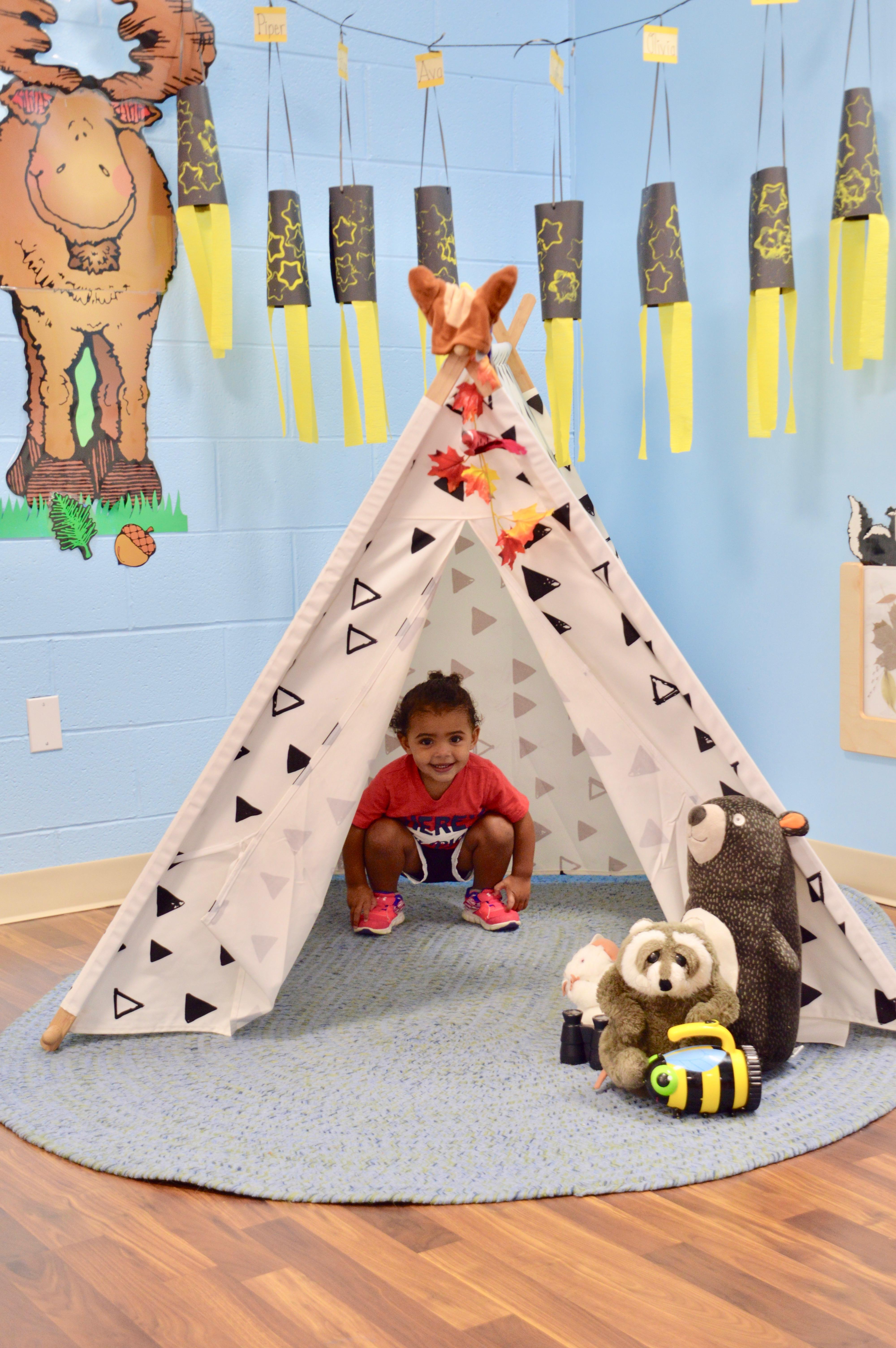 toddler sitting in a tepee