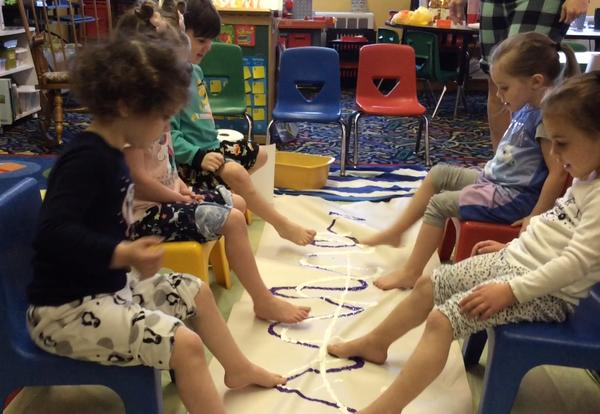 students painting with their feet