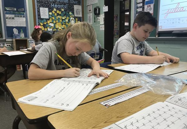 students practicing cursive