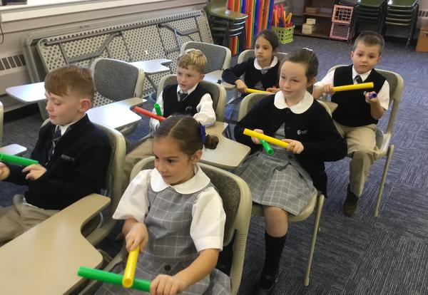 students in music class with rhythm sticks