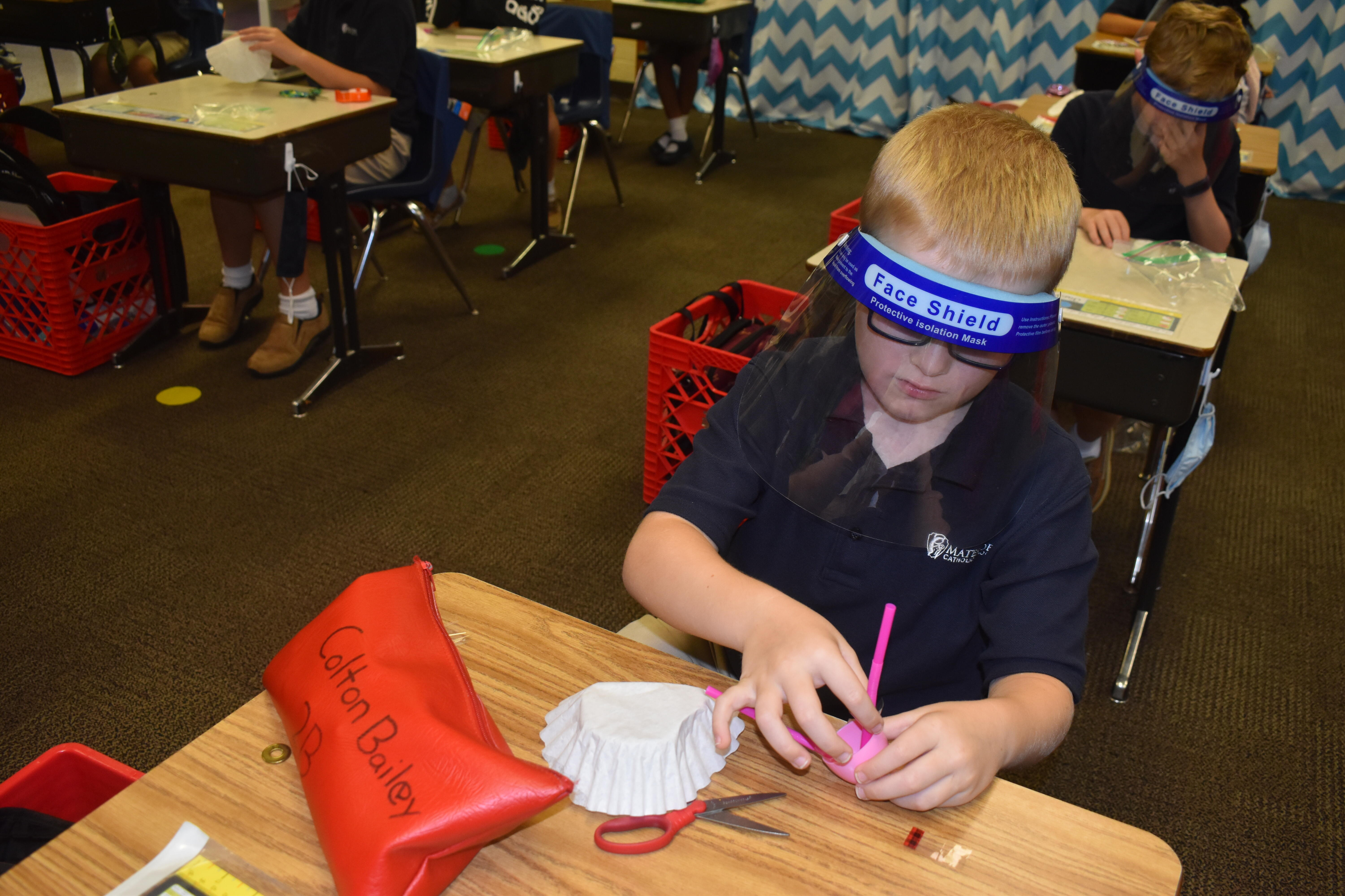 second graders make aluminum boats to hold hearts.