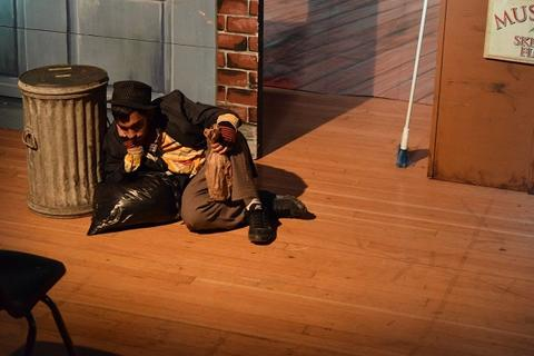 Student dressed as hobo lies by trash can, face propped on one fist