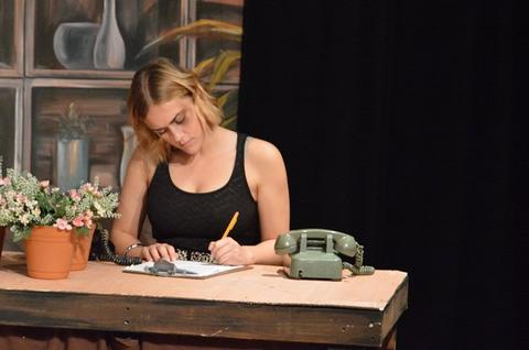 Student in black tank top sits at desk and writes with pencil, next to a green rotary dial telephone