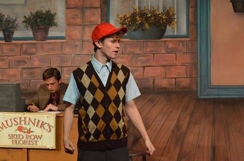 Student wearing red baseball cap and argyle sweater vest, in play