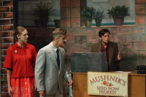 Female student in red dress, male student in suit and tie with fake moustache, and second male student in brown suit and purple shirt; all look upset