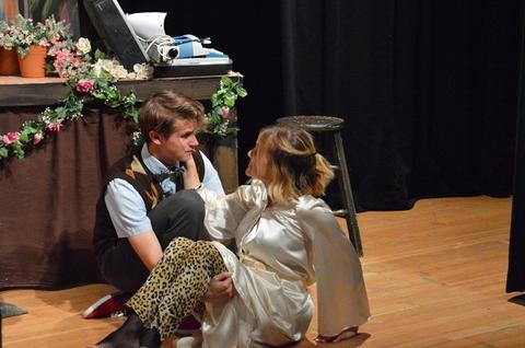 Student in argyle sweater vest and student in shiny dress having meaningful conversation