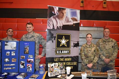 Military recruiters at a fair in the gym
