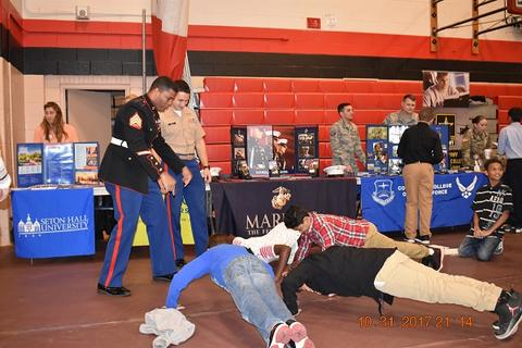 Students doing pushups at Marine booth during College Fair