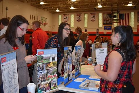 Student talks to college rep in gym