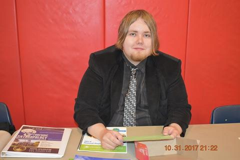 College rep in black suit sits behind table