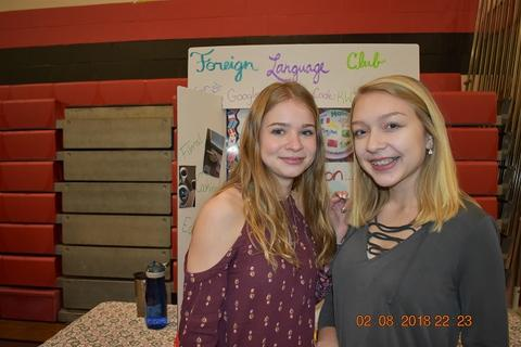 Two students smiling in front of Foreign Language Club booth