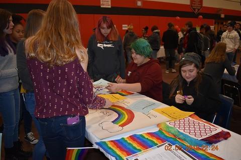 Students around rainbow sign