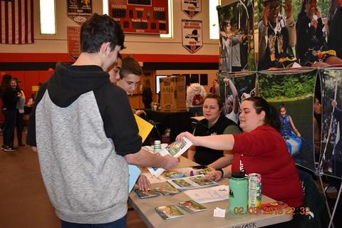 Student receiving material at booth