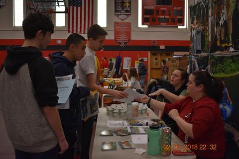 Vendor sharing info with students at fair.