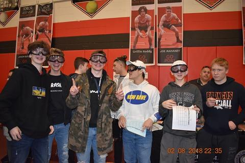 Students with safety goggles pose at fair