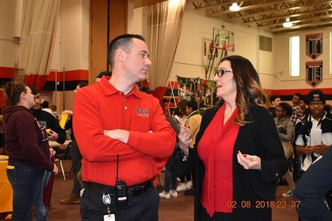 Adults in red shirts speak with each other in gym