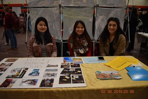 Three students working booth for Rotary Interact Club