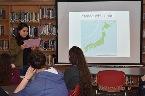 Student talking about Japan next to slide of map with Yamaguchi, Japan