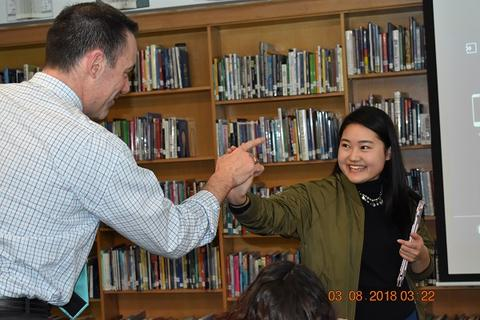 Teacher smiling and pointing a finger at Japanese exchange student