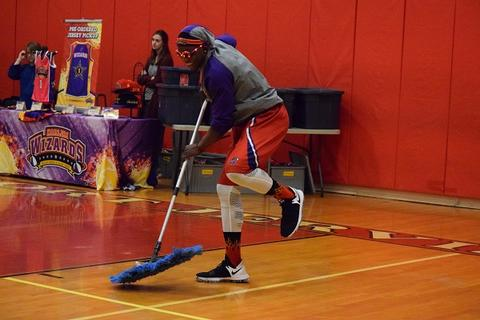 Wizards member pushing dust mop and laughing