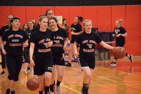 Women basketball players wearing uniforms and dribbling basketballs