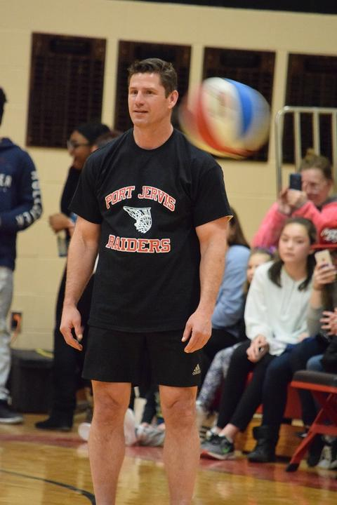 Male basketball player stands while ball is in motion