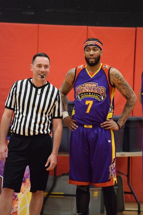 Wizards player standing with arms on hips, next to referee