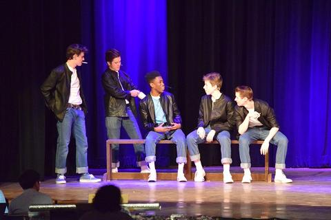 Actors playing the T-Birds wear black jackets, white t-shirts, and jeans