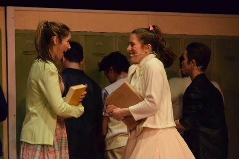 "Two female characters talking excitedly in hallway during ""Grease"""