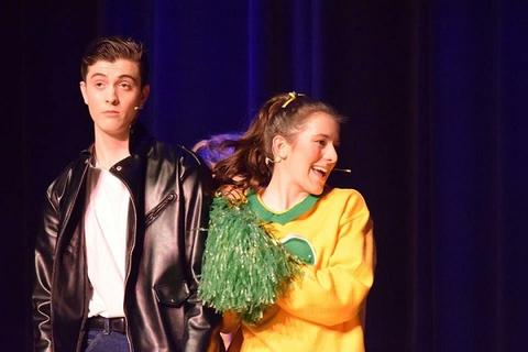 "Danny looks confused, actress looking away from camera, during ""Grease"""
