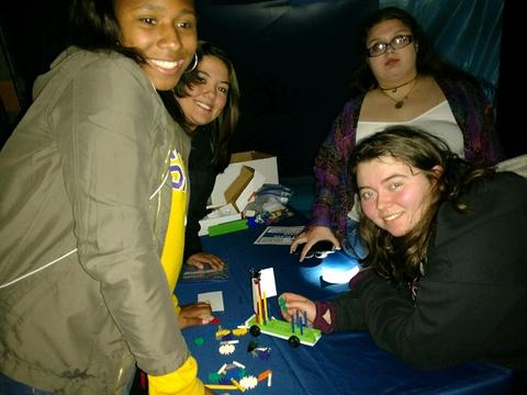 Four female students working on a challenge with toy pieces to build a car