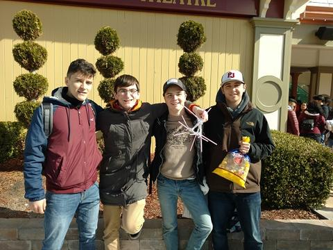 Group of students pose with egg structure and bag of popcorn
