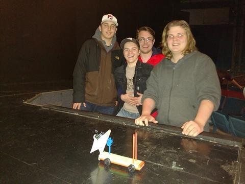 Group of four male students smile and pose with car structure, placed on stage.