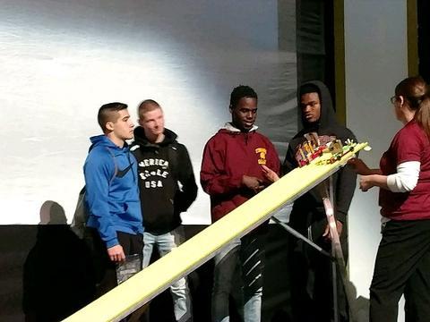 Student demonstration of how car will run along white ramp
