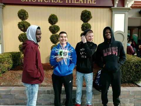 Four male students pose and smile in front of round bulb topiaries