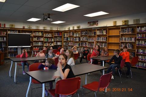 Students listen at tables in library