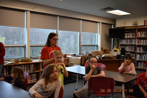 Adult talks with students in library