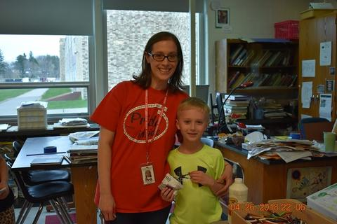 Adult female with red shirt and glasses with male child; both are smiling