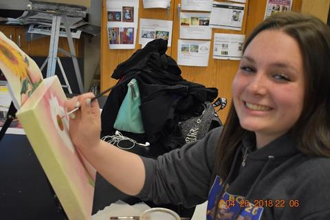 Teen female is painting on a small canvas and smiling at camera