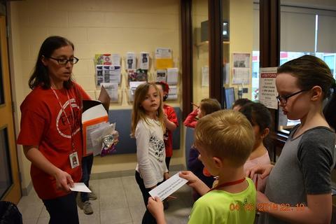 Adult female handing slips of paper to children