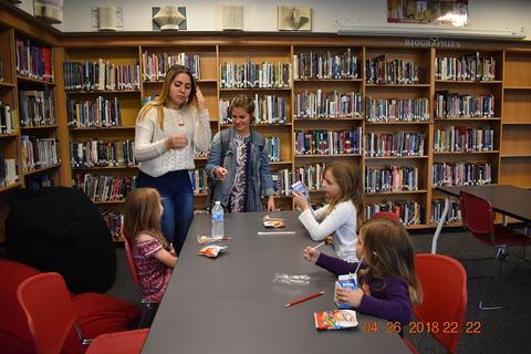 Adults and children speaking at library table