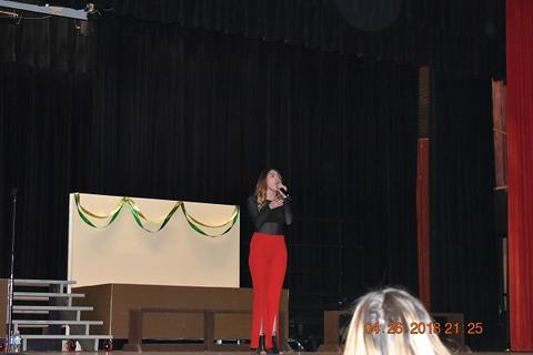 Kendyle Page stands on stage speaking in mic