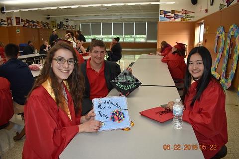 Three graduates at table, smiling