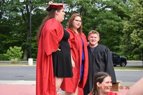 Three grads in gowns standing